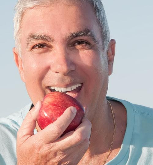 Senior man eating an apple